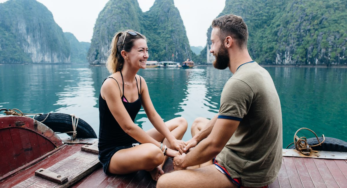 Couple holding hands and smiling on the deck of cruise ship with view on Ha long Bay and calm sea. People travel in Vietman.